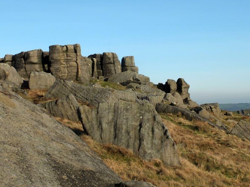Grote ruwe gritstonedagzomende aardlaag bij bridestones een grote rotsvorming in de blauwe hemel van West-Yorkshire dichtbij todm stock afbeelding