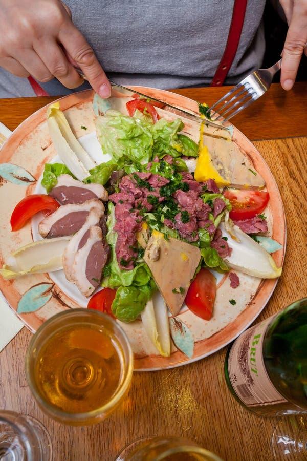 Grote salade met foiegras en glas cider stock fotografie