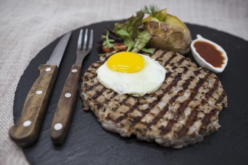 Grote, sappige, heerlijke biefstuk met een gebraden ei en aardappelen in de schil op een steenplaat stock foto's