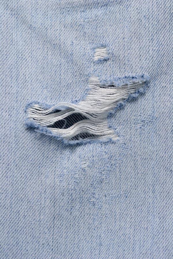 Grote scheur op oude jeans. stock foto's