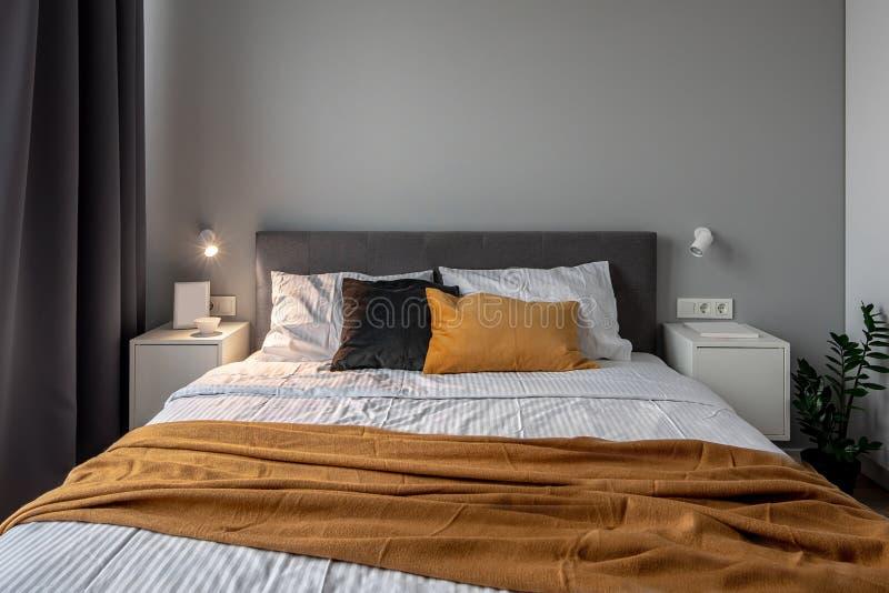 Grote slaapkamer in moderne stijl met grijze en witte muren en lichtgevende lamp royalty-vrije stock foto