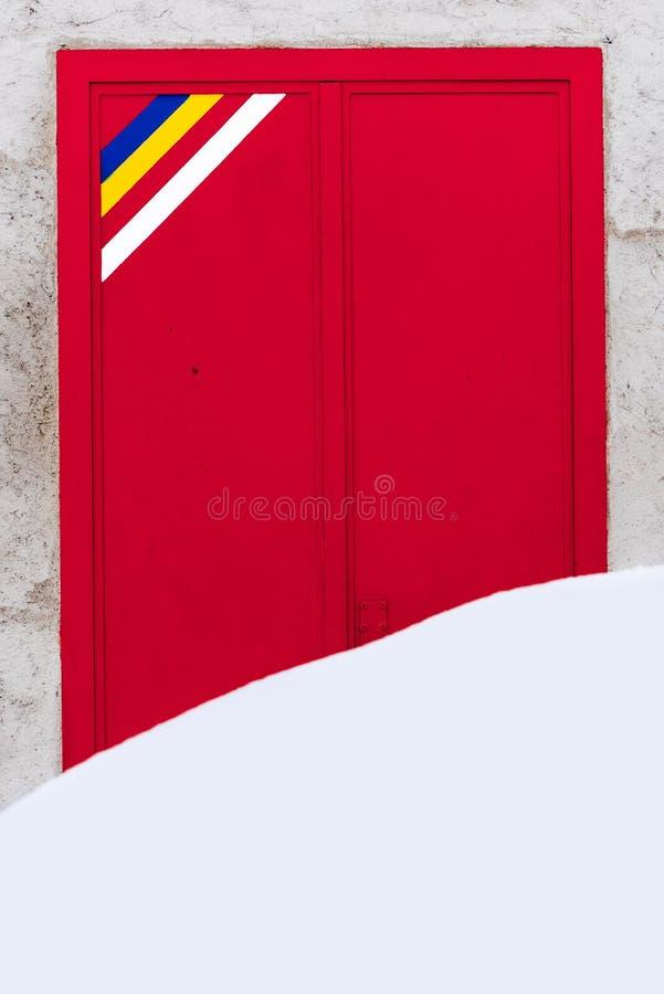 Grote stapel die van sneeuw de ingang van een grote metaal rode deur behandelen stock foto's