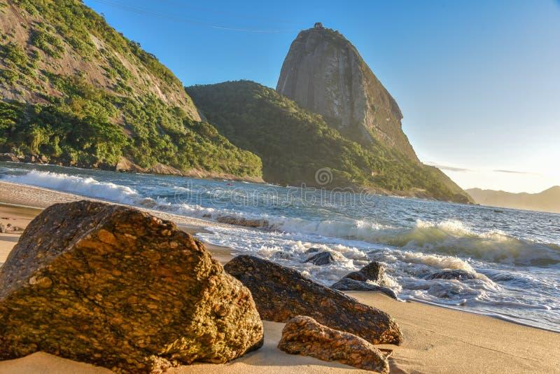 Grote stenen bij het verlaten Strand van Praia Vermelha en zonsopgang met de heldere zon die de Sugarloaf-Berg verlichten stock afbeelding