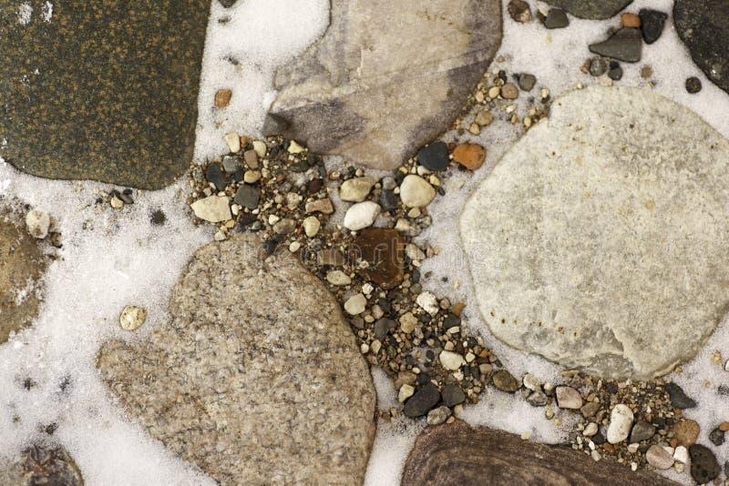 Grote stenen in de sneeuw stock afbeelding