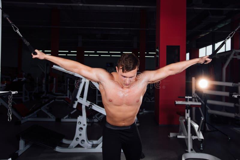 Grote sterke bodybuider zonder overhemden toont oversteekplaatsoefeningen aan De pectoral spieren en hard opleiding royalty-vrije stock foto's
