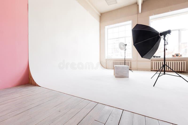 Grote studio ruimte witte cyclorama en natuurlijk licht van grote vensters verlichtingsmateriaal en flits royalty-vrije stock afbeelding