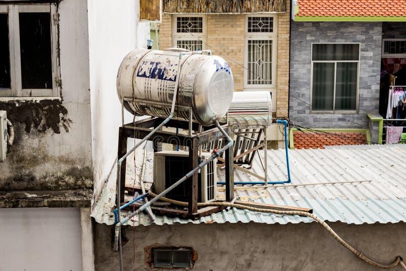 Grote tank met water op het dak van het slechte die huis voor het milieuwater verwarmen zonder elektriciteit wordt gebruikt stock foto