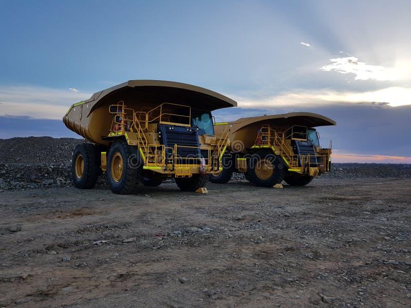 Grote van de aarde bewegende vrachtwagens van de mijnmijnbouw de bouwschemering stock foto