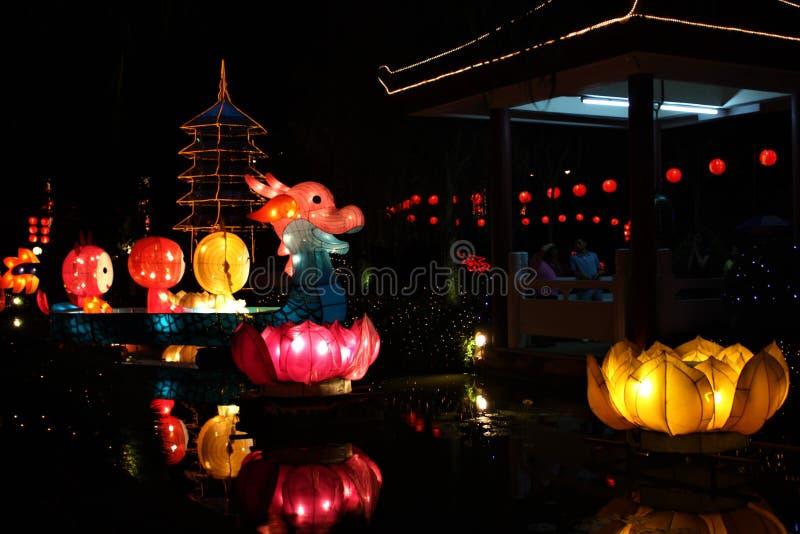Grote veelkleurige draakdocument lantaarns die op water bij nacht drijven stock foto
