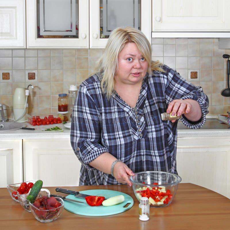 Grote vrouw in keuken stock afbeelding