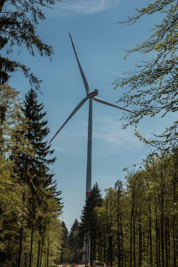 Grote windmolens voor windenergie dichtbij het dorp stock foto's