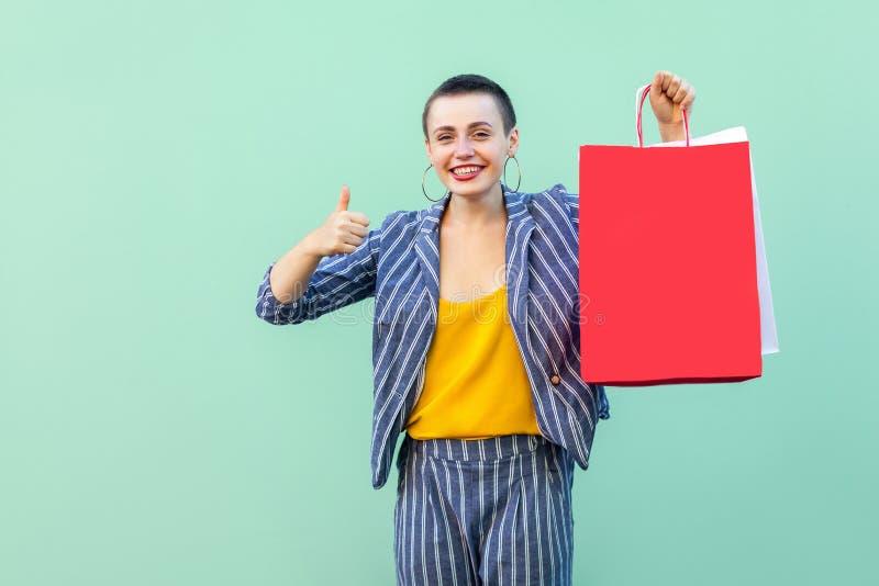 Grote winkel Portret die van succesvolle mooi met korte haar jonge vrouw in gestreept kostuum die, rode het winkelen zak houden b royalty-vrije stock fotografie