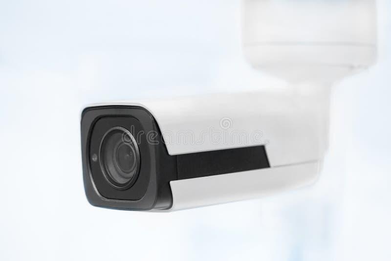 Grote witte professionele toezichtcamera Kabeltelevisie opgezet op plafond Veiligheidssysteemconcept Copyspace, neutrale lichtbla stock afbeeldingen
