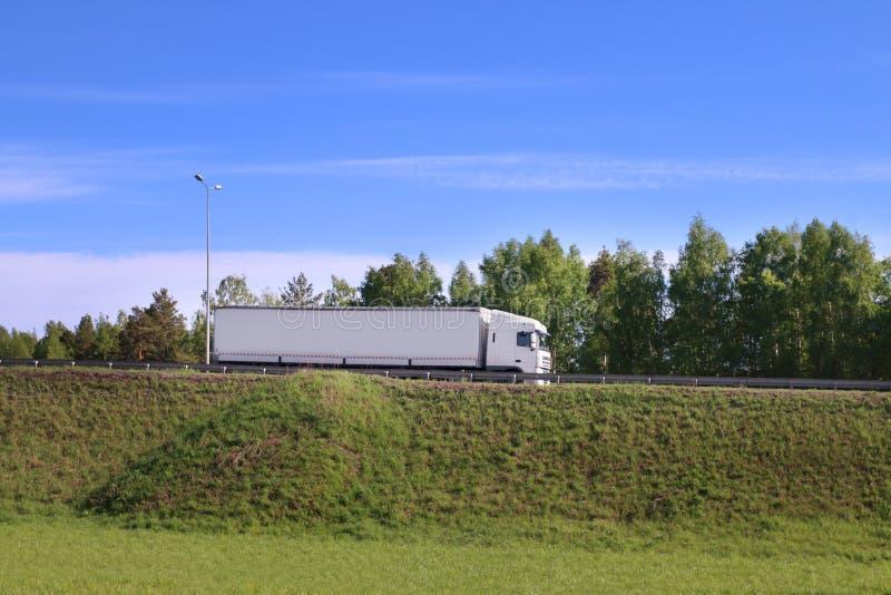 Grote witte vrachtwagenbewegingen op weg op heuvel in groen gras stock foto's