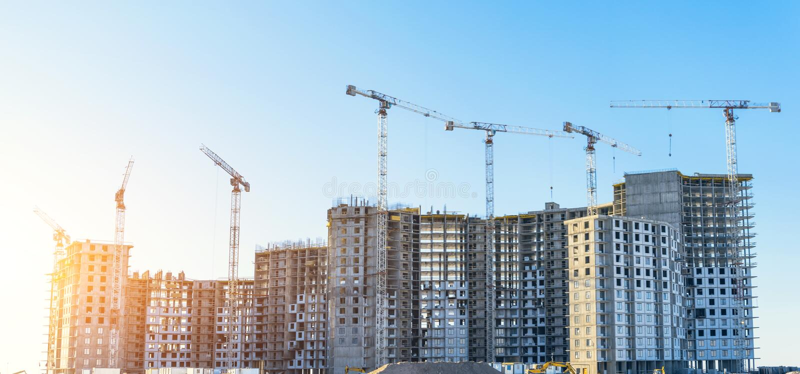 Grote woon complexe onroerende goederenflats, in aanbouw met hoge kranen De mening van het panorama stock afbeeldingen
