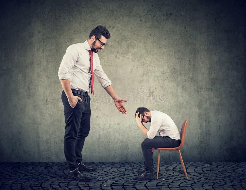 Grote zakenman die een hand ondersteunend een gedeprimeerde wanhopige kerel geven stock fotografie