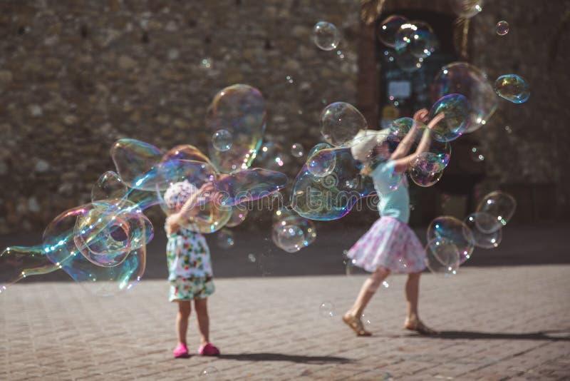 Grote zeepbelsvlieg in de lucht buiten Kinderen die op de achtergrond in de zomerdag spelen stock afbeeldingen