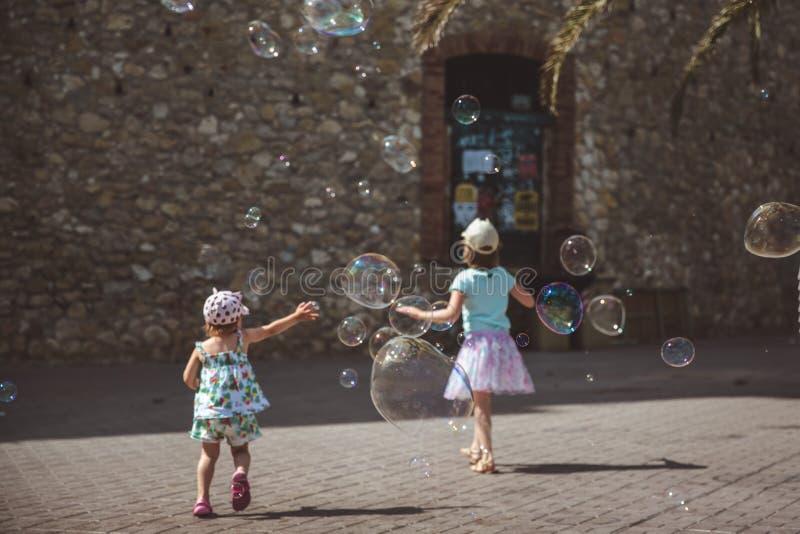 Grote zeepbelsvlieg in de lucht buiten Kinderen die op de achtergrond in de zomerdag spelen royalty-vrije stock fotografie