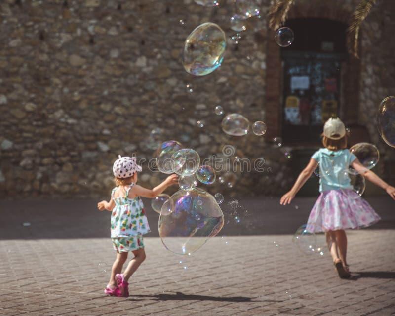 Grote zeepbelsvlieg in de lucht buiten Kinderen die op de achtergrond in de zomerdag spelen royalty-vrije stock afbeelding