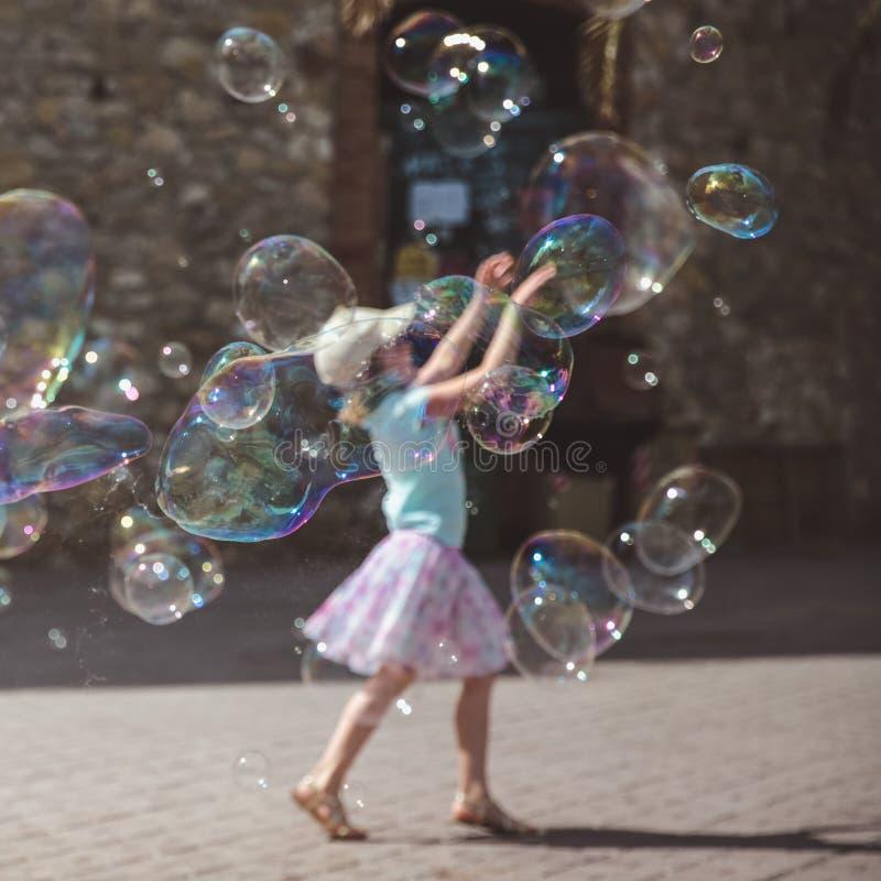 Grote zeepbelsvlieg in de lucht buiten Meisje het spelen op de achtergrond in de zomerdag royalty-vrije stock afbeelding