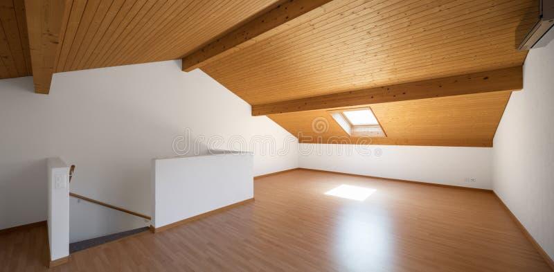 Grote zolder met houten vloeren en blootgestelde stralen stock fotografie