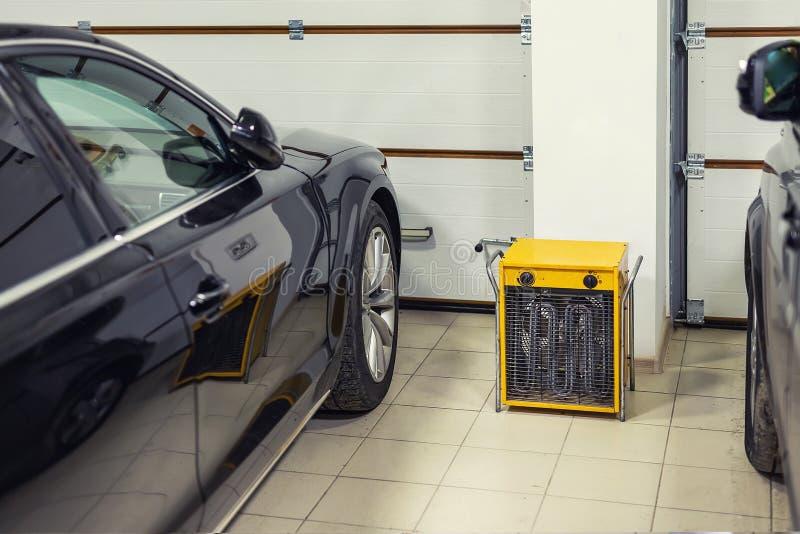 Grote zware industriële elektrische ventilatorverwarmer in het dubbele binnenland van de autogarage Twee die voertuigen voor de w royalty-vrije stock afbeelding