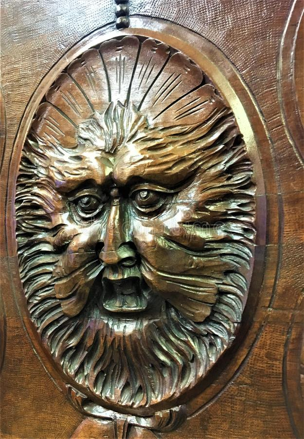 Grotesque mask into a castle, wood, face and magic. Sculpture, art work, craftsmanship, eyes, mouth, expression, masterpiece, beauty mystery, arcane, interior stock photo