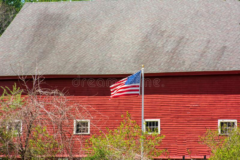 American Flag  blowing briskly in from of bright red barn on a sunny spring day royalty free stock images