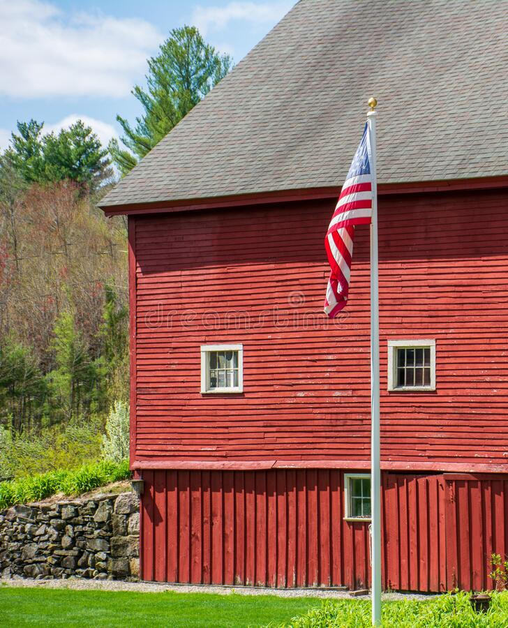American Flag unfurling slowly in from of bright red barn and  a green forest stock photography