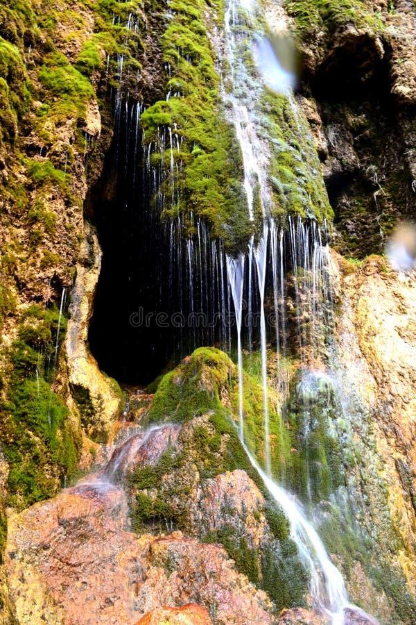 Grottaingång som döljas bak en liten vattenfall Stalaktitgrotta i bergen av det norr Kaukasuset, Ryssland royaltyfri foto