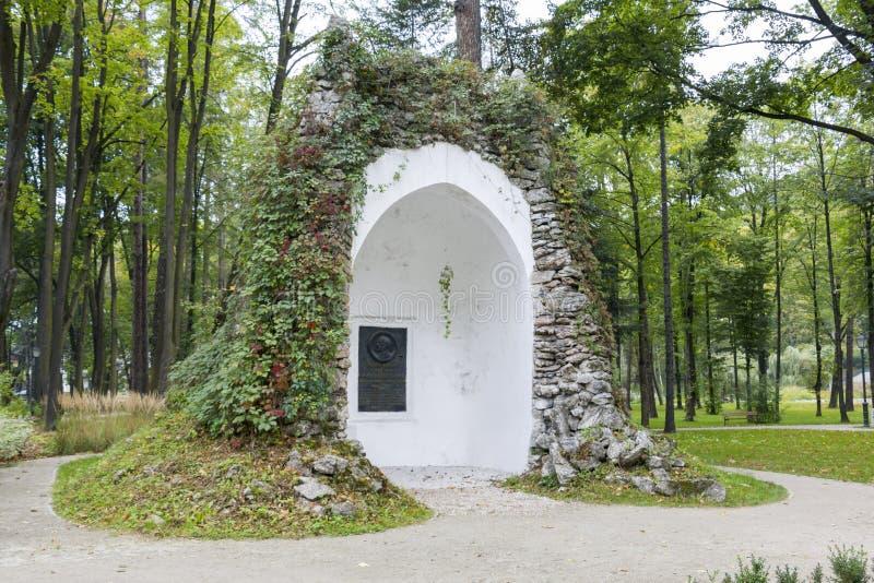 Grottan med en platta som firar minnet av Mikolaj Zyblikiewicz i lägre, parkerar i Szczawnica, Polen royaltyfria bilder