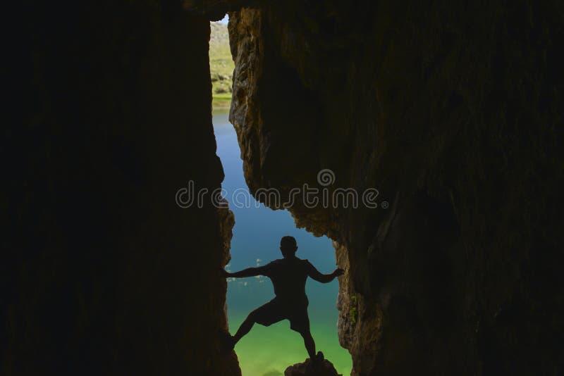 Grottautforskare som ut ser från grottan royaltyfri bild