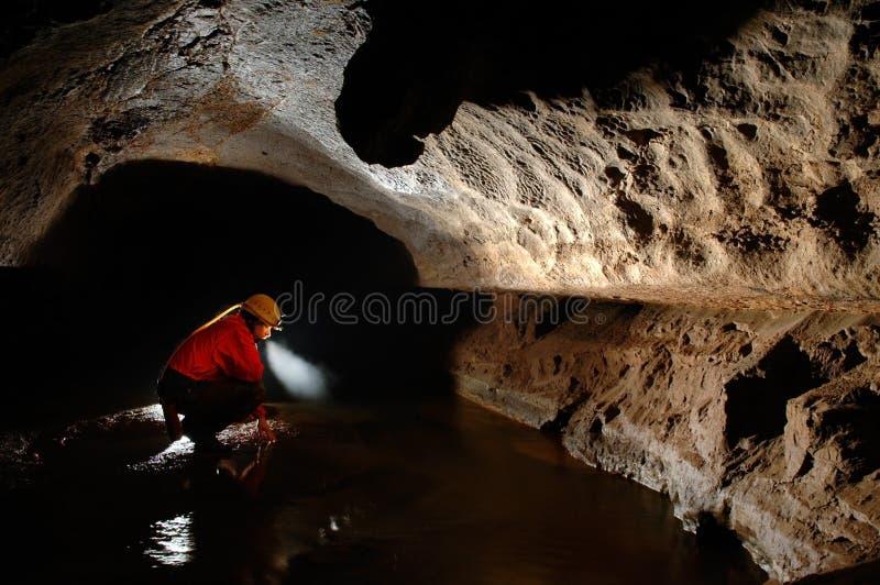 Grottautforskare, speleolog som undersöker tunnelbanan royaltyfri bild