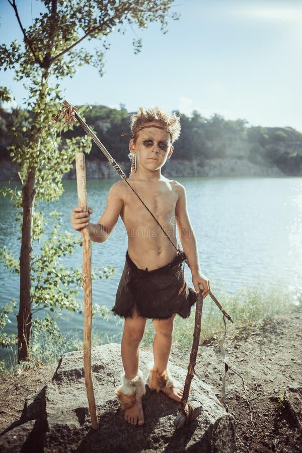 Grottmänniska, manlig pojke med stenyxan och pilbågejakt utomhus royaltyfri fotografi