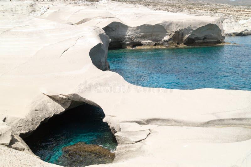 Grottor och vaggar bildande vid havet på Sarakiniko område royaltyfria bilder