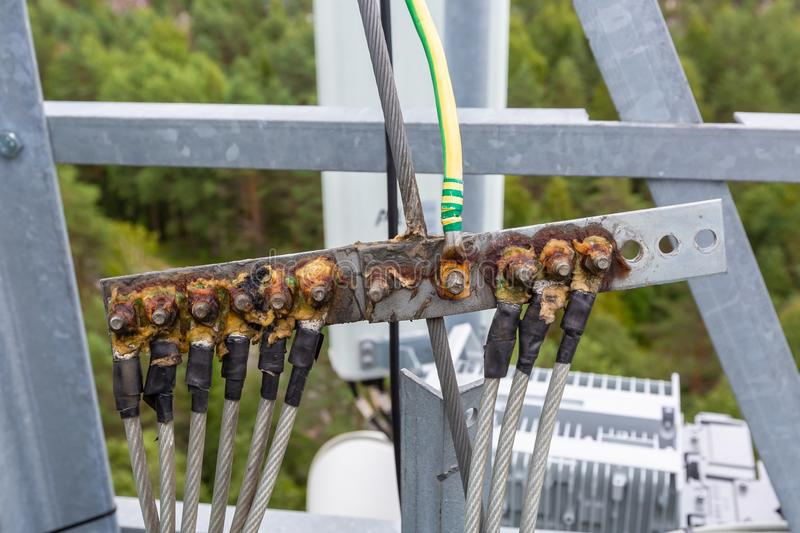 Ground bar with metal hawsers and solid oil for grounding telecommunication equipment of basic station is a part of royalty free stock image