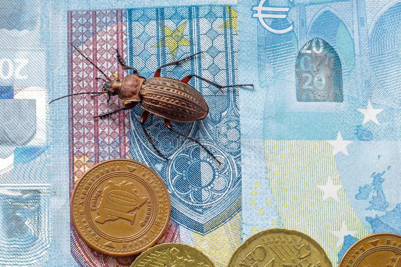 Ground beetle on the bill twenty euros, small coins of Europe. Concept: money beetle stock image