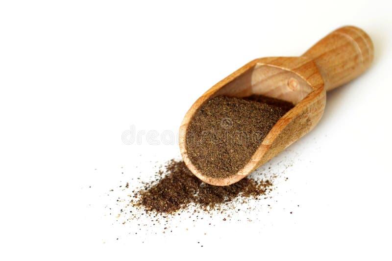 Ground black pepper. In wooden scoop stock image