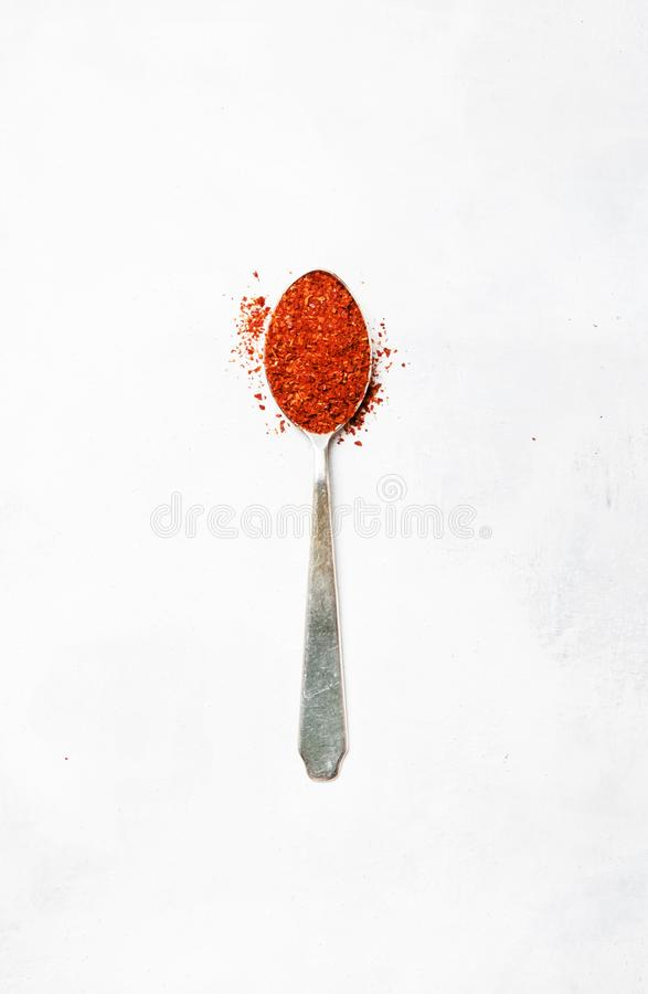 Ground chili pepper in a silver spoon, minimalist style, spice b stock image
