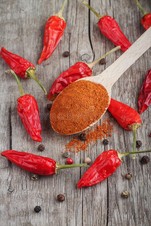 Ground chilli pepper on wooden spoon. Ground red chili peppers and allspice on a wood royalty free stock image