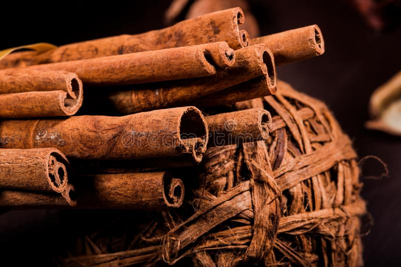 Ground cinnamon, cinnamon sticks, connected with a tray with a bow on a color background in a rustic style. Macro photo. With selective focus. Close up food royalty free stock photography
