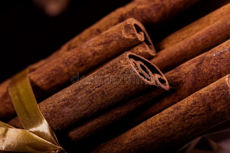 Ground cinnamon, cinnamon sticks, connected with a tray with a bow on a color background in a rustic style. Macro photo. With selective focus. Close up food royalty free stock photos