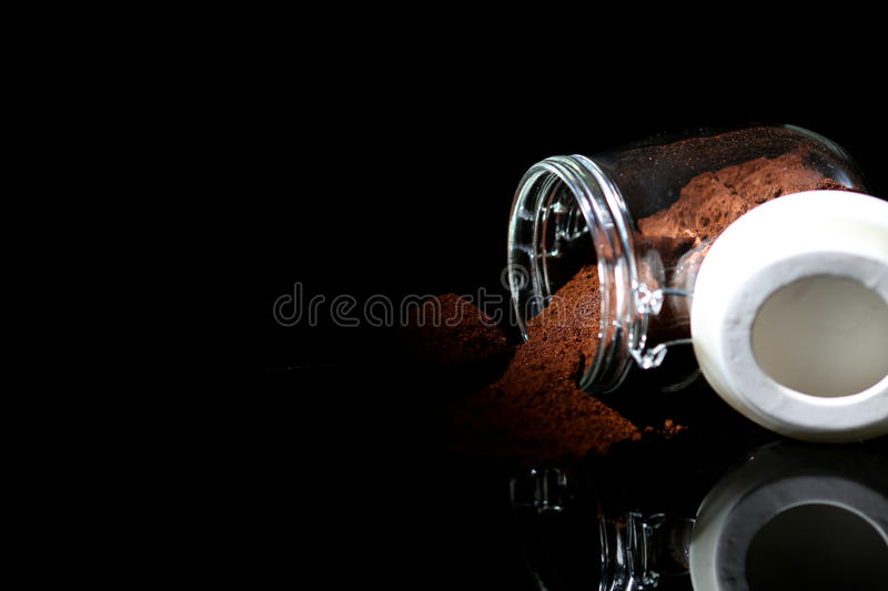 Ground coffee in a glass jar. Grounded coffee pouring out from the jar royalty free stock photography