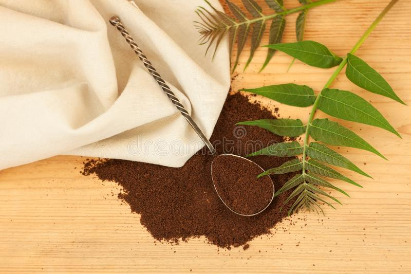 A ground coffee with linen fabric, an antique spoon, palm brunch. High quality roasted ground coffee beans. A ground coffee with linen fabric towel, an antique royalty free stock photos