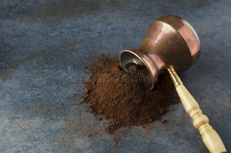 Ground coffee spilling from turkish coffee pot on grey surface,empty space for text. Ground coffee,turkish coffee pot,grey table,closeup Ground coffee spilling royalty free stock image