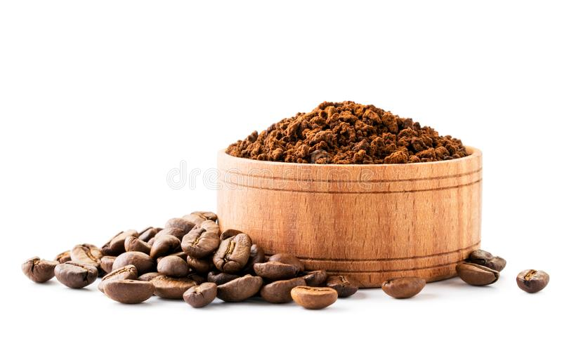 Ground coffee in a wooden plate and coffee beans on a white background. royalty free stock photos