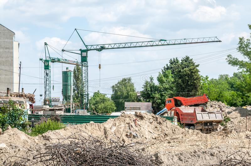 Ground excavation site with heavy tipper trucks and construction cranes on the new residential building terrain preparation, with. Blue sky background royalty free stock image