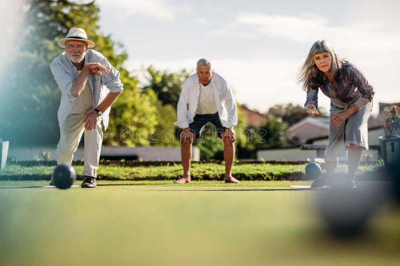Elderly couple playing boules in a park royalty free stock images