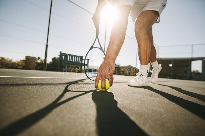 Man bending down to pick a tennis ball. Ground level view of a man picking a tennis ball on a sunny day. Low angle view of a tennis player bending forward to royalty free stock image