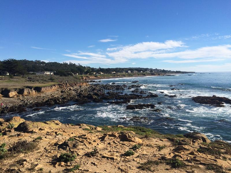 Cambria overview of rocky shoreline against the tide. Ground-level view of the tide meeting a rocky shoreline. Image taken before noon stock images